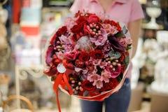Florista que sostiene un ramo brillante grande en los tonos rojos que consisten en rosas y otras flores hermosas Fotografía de archivo
