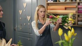 Florista rubio en delantal con su compañero de trabajo en el contador en tienda floral mientras que arregla contando el precio pa metrajes