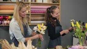 Florista rubio sonriente en el delantal que se coloca con su compañero de trabajo en el contador en tienda floral mientras que ar metrajes