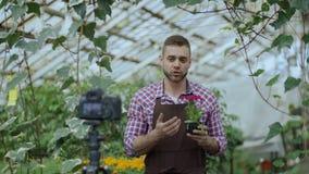 Florista sonriente joven del hombre del blogger en el delantal que sostiene el blog video de la flor que habla y de registración  metrajes