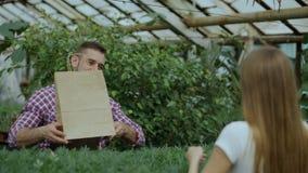 Florista sonriente joven del vendedor que trabaja en centro de jardinería El hombre da el panier al cliente y pago de la fabricac almacen de video