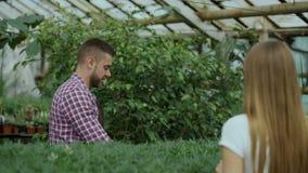 Florista sonriente joven del vendedor que trabaja en centro de jardinería El hombre da el panier al cliente y pago de la fabricac metrajes