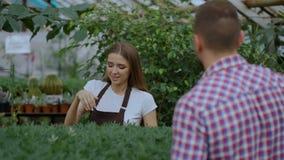 Florista sonriente joven del vendedor que trabaja en centro de jardinería La mujer da el panier al cliente y pago de la fabricaci almacen de video