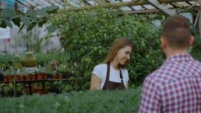 Florista sonriente joven del vendedor que trabaja en centro de jardinería La mujer da el panier al cliente y pago de la fabricaci metrajes