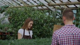 Florista sonriente joven del vendedor que trabaja en centro de jardinería La mujer da el panier al cliente y pago de la fabricaci almacen de metraje de vídeo