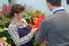Floristas de sexo masculino y de sexo femenino que trabajan en invernadero fotos de archivo
