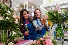 Floristas fêmeas que arranjam flores imagem de stock royalty free