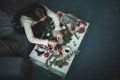 Floristen-Woman Making Christmas-Dekorationen zu Hause lizenzfreie stockfotografie