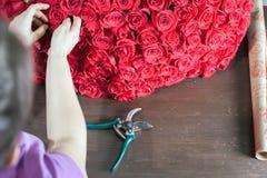 Floristenfrau bereitet einen großen Blumenstrauß von roten Rosen vor Stockfotografie