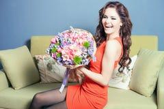 Floristenfrau bereitet einen großen Blumenstrauß von roten Rosen vor Stockbild