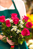 Floristenfrau, die Blumenstraußhände der roten Rosen anhält Stockfotos