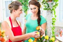 Floristenfrau, die rosafarbenen Blumenstrauß an ihren Kunden verkauft Stockbilder