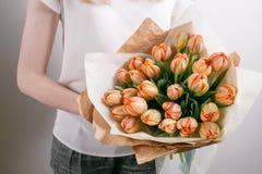 Floristenmädchen mit Pfingstrosenblumen oder orange Blumenblumenstrauß der jungen Frau der Tulpen für Geburtstagsmuttertag Lizenzfreies Stockbild
