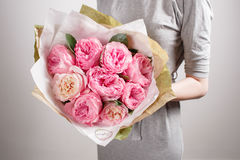 Floristenmädchen mit Pfingstrosenblumen oder rosa Gartenrosen Blumenblumenstrauß der jungen Frau für Geburtstagsmuttertag Lizenzfreie Stockfotografie
