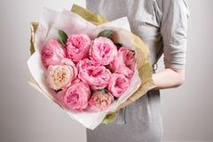 Floristenmädchen mit Pfingstrosenblumen oder rosa Gartenrosen Blumenblumenstrauß der jungen Frau für Geburtstagsmuttertag Lizenzfreies Stockbild