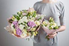 Floristenmädchen mit reichen Bündelblumen Frischer Frühlingsblumenstrauß Blaues Meer, Himmel u Blume der jungen Frau für Geburtst Stockfotos