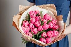 Floristenmädchen mit Pfingstrosenblumen oder rosa Blumenblumenstrauß der jungen Frau der Tulpen für Geburtstagsmuttertag Lizenzfreie Stockfotos