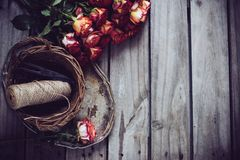 Floristic background. A bouquet of roses, scissors and twine in a basket on an old vintage wooden board Stock Photos