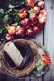 Floristic background. A bouquet of roses, scissors and twine in a basket on an old vintage wooden board Stock Images