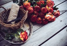 Floristic background. A bouquet of roses, scissors and twine in a basket on an old vintage wooden board Stock Photo