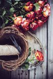 Floristic background. A bouquet of roses, scissors and twine in a basket on an old vintage wooden board Royalty Free Stock Image