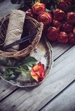 Floristic background. A bouquet of roses, scissors and twine in a basket on an old vintage wooden board Royalty Free Stock Photography