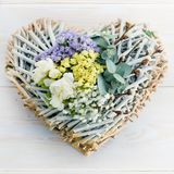 Floristic composition of the heart with fresh flowers on a wooden background royalty free stock photo