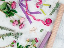 Floristic flat lay with flowers. Floristic flat lay. Flowers, wrapping paper, ribbons and Love you wooden sign on gray tabletop. Roses, eucalyptus, Copy space stock photos