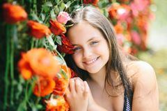 Floristic, floral decor, design, flower shop. Girl smile with red roses, beauty. Beauty, spring, summer season. Little child with flowers, spring Valentines stock photo