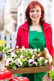 Floristin mit Pflanzen Lieferung vor Laden Royalty Free Stock Image