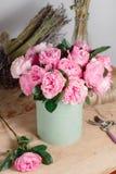 Floristischer Hintergrund der Weinlese, bunte Rosen, antike Scheren und ein Seil auf einem alten Holztisch Stockfoto