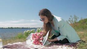 Floristry, menina nova do florista nos monóculos faz o ramalhete bonito de flores delicadas frescas e o envolvimento no papel sob vídeos de arquivo
