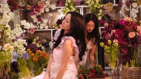 Florists. Asian women happy working in flower store. Florists. Florists. Two asian women happy working in flower store indoors. Playful fashion models in tender stock footage