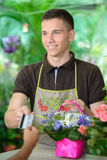 Florists. Young man working as florist giving credit card to customer after purchase Royalty Free Stock Image