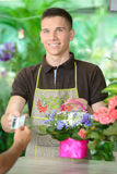 Florists. Young man working as florist giving credit card to customer after purchase Stock Photo