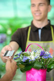Florists. Young men working as florist giving credit card to customer after purchase Royalty Free Stock Photo
