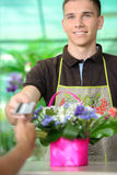 Florists. Young men working as florist giving credit card to customer after purchase Royalty Free Stock Images