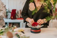 Flosist que trabaja con las rosas rojas, tomando medidas Foto de archivo libre de regalías