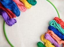 Floss colorido do bordado em um fundo do bordado com esboço branco Imagem de Stock Royalty Free