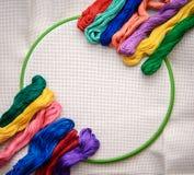 Floss colorido do bordado em um fundo do bordado com esboço branco Fotografia de Stock Royalty Free