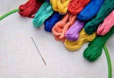 Floss colorido do bordado em um fundo do bordado com esboço branco Foto de Stock