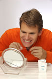 Floss for healthy teeth and gums. Man holds floss while examining teeth in front of mirror Stock Image