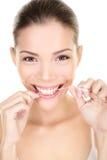 Flossing tänder för kvinna som ler genom att använda tandtråd Arkivfoton