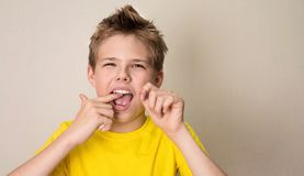 Flossing Zähne des Jungen Nahaufnahmeporträt des jugendlich Jungen mit zahnmedizinischem Florida lizenzfreies stockfoto