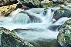 Flot de montagne montant en cascade au-dessus des roches Photo stock