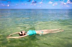 Flotación de relajación de la mujer en el océano Fotos de archivo