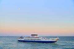 Flotación en el transbordador del mar en la puesta del sol Imagen de archivo libre de regalías