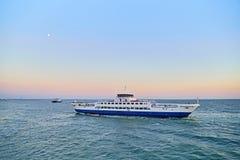 Flotación en el transbordador del mar en la puesta del sol Imágenes de archivo libres de regalías