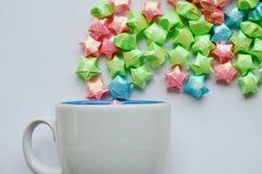 Flotación de papel de la estrella colorida de la taza de café en el fondo blanco Imagen de archivo
