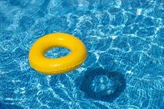 Flotador amarillo de la piscina, anillo de la piscina en refreshi azul fresco Fotos de archivo libres de regalías